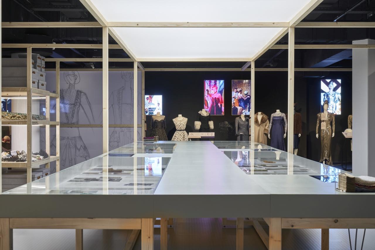 Ausstellungsansicht großer Vitrinentisch mit Kostümen im Hintergrund