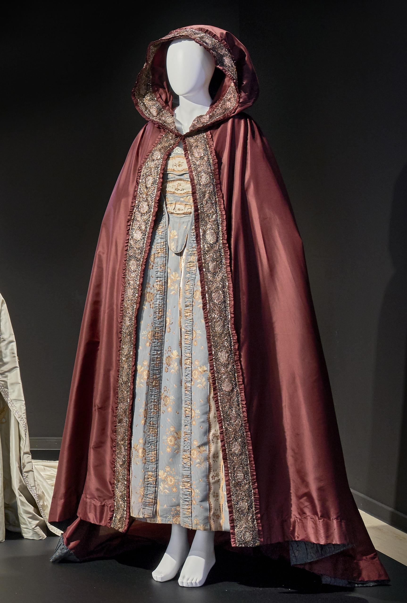 Katharina die Große: Dreiteiliges, hellblaues Tageskleid aus Baumwoll-Damast und bordeauxfarbenes Seidencape mit großer Kapuze und langer Schleppe in goldgelb und goldbraun
